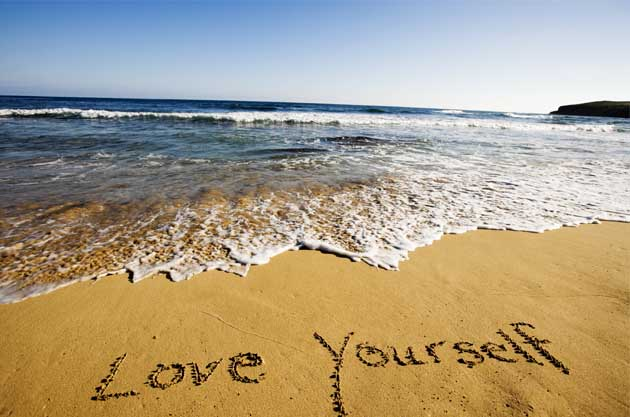 love yourself written in the sand